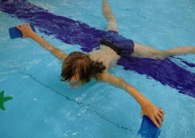 Junge liegt auf Bauch im Wasser