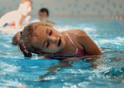 Mädchen neigt sich mit rechtem Ohr über die Wasseroberfläche