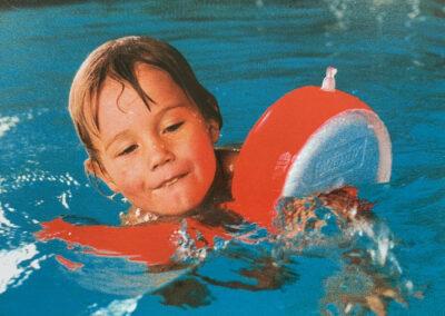 Junge mit Schwimmflügeln im Wasser