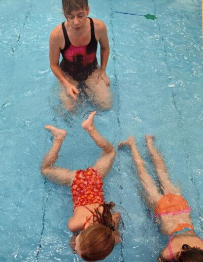 Dr. Lilli Ahrendt übt Schwimmbewegungen mit zwei Mädchen